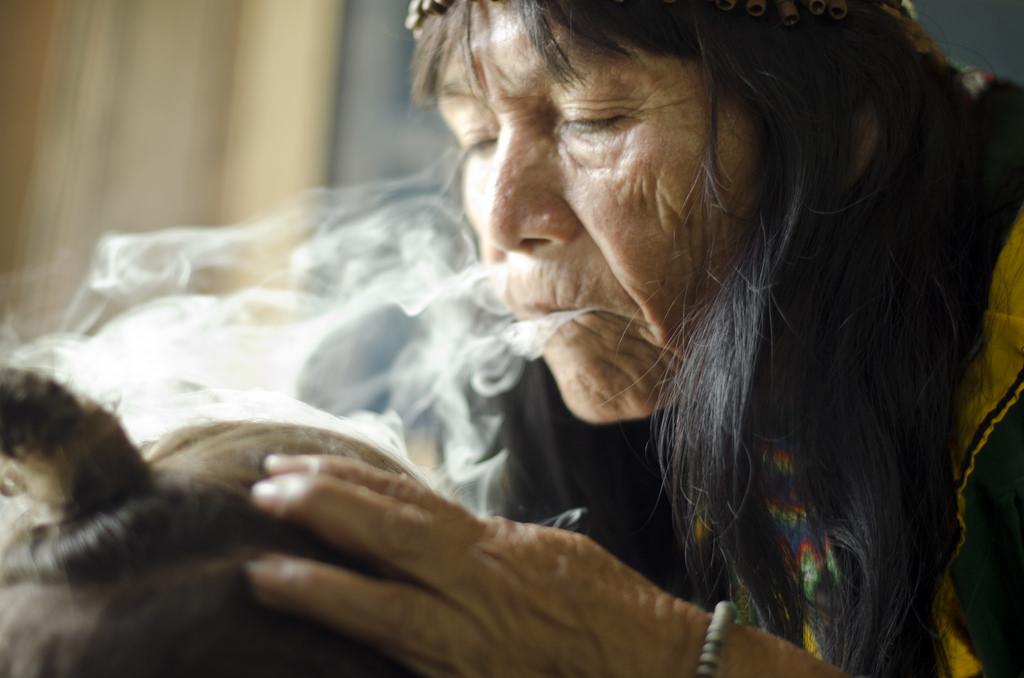 sciamana shipibo proteggendo un paziente con fumo di tabacco